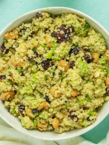 overhead photo of quinoa salad with cranberries, avocado, cashews, and green onion in a white bowl