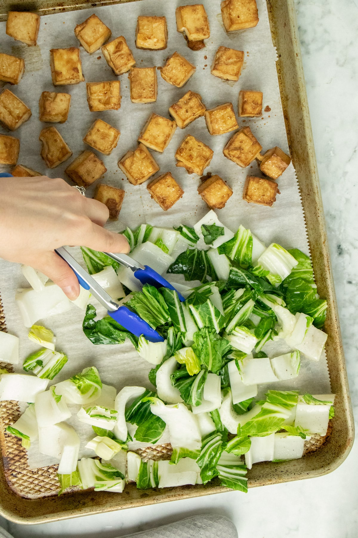 hand using blue tongs to stir the bok choy on a baking sheet next to tofu cubes