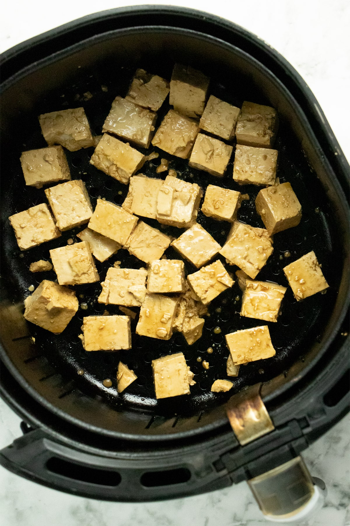 marinated tofu in a black air fryer basket