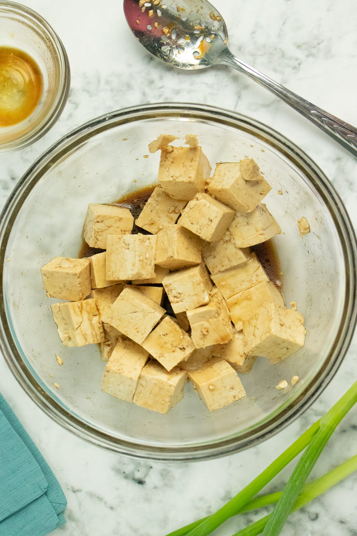 glass bowl of cubed tofu marinating next to a large spoon