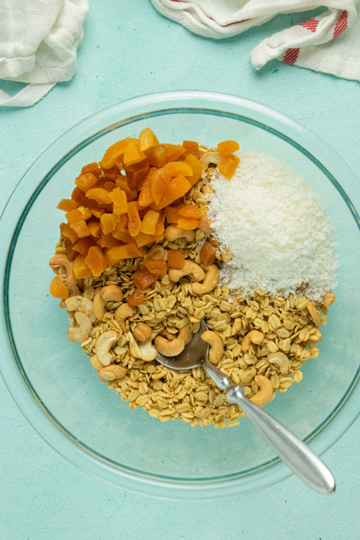 overhead photo of cooked granola with apricots and shredded coconut, before stirring