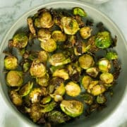serving dish of air fryer brussels sprouts on a marble tabletop
