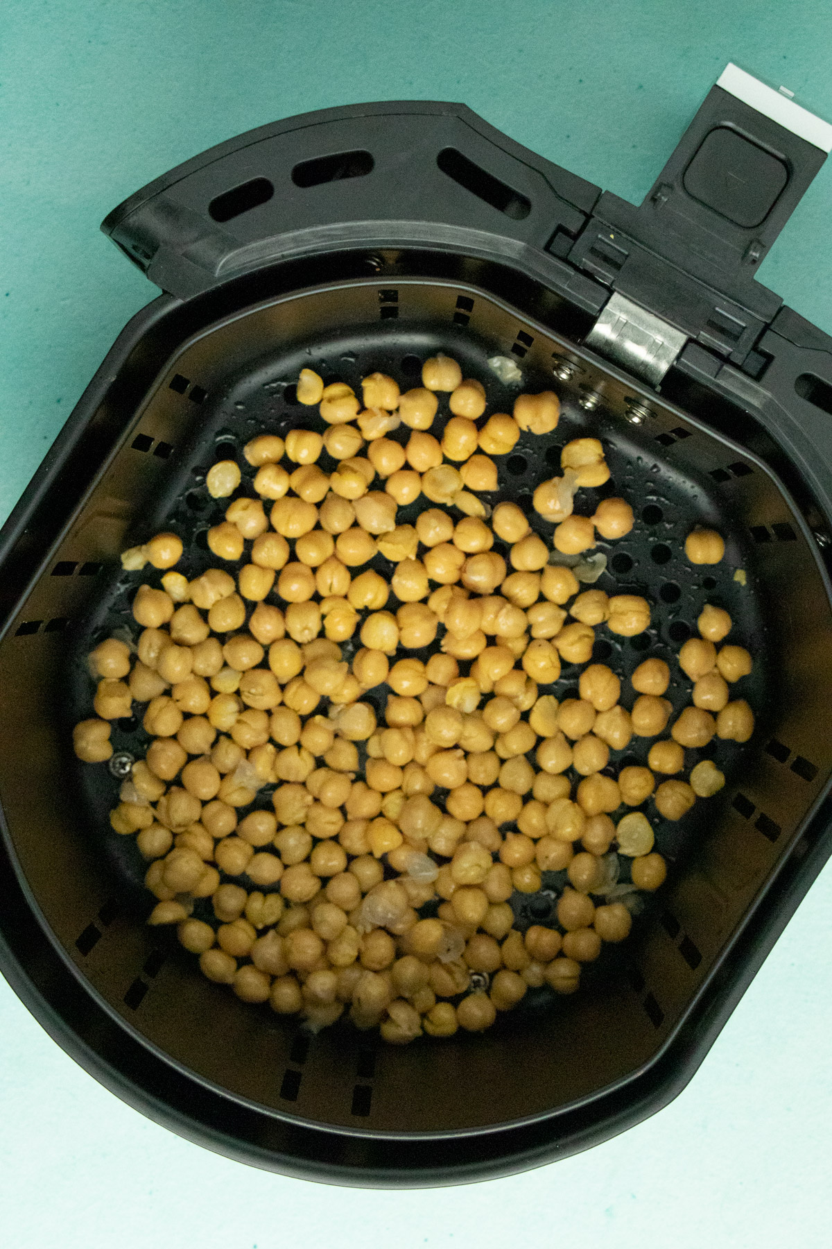 uncooked chickpeas in the air fryer basket