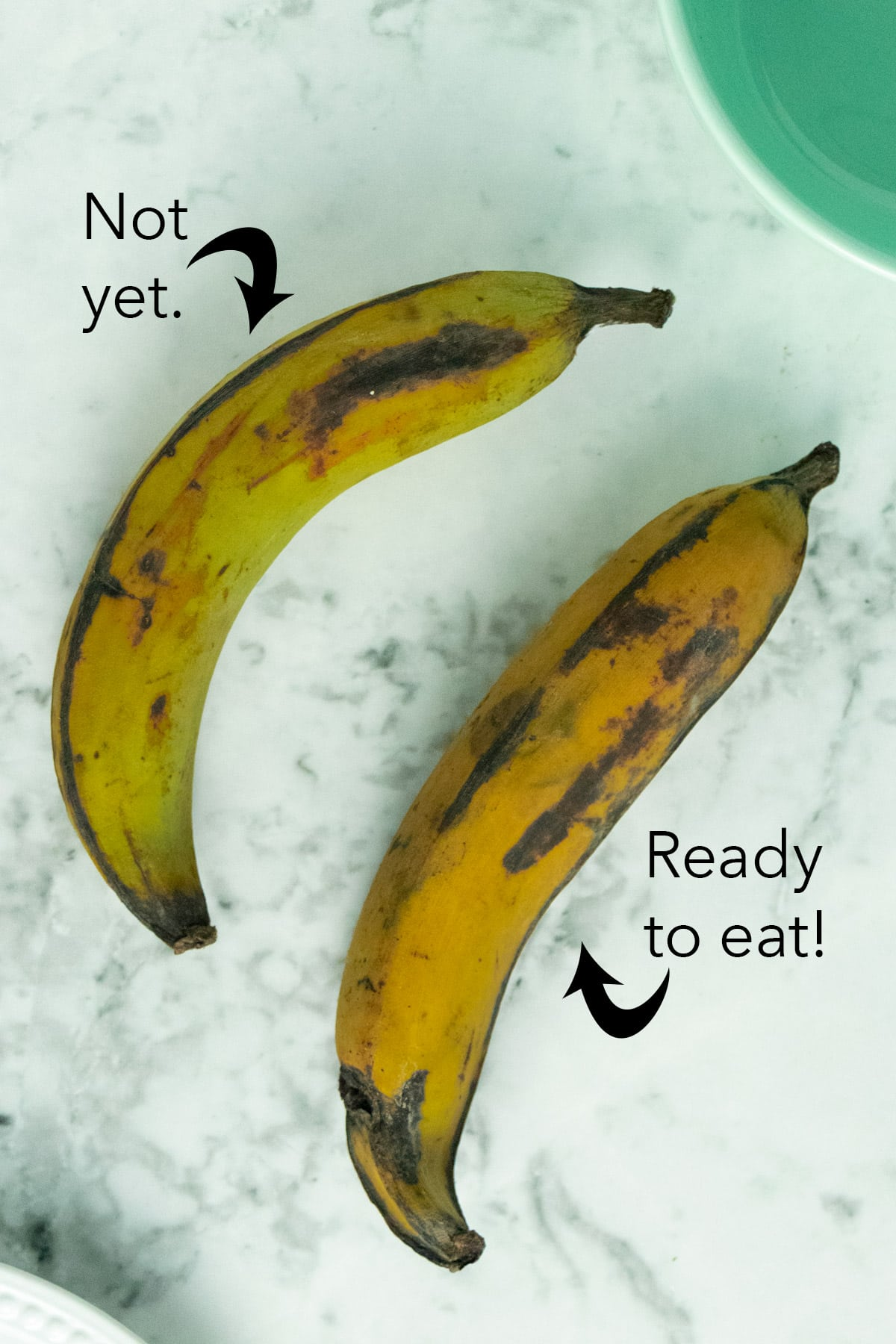 two plantains on a marble tabletop, one ripe, one not
