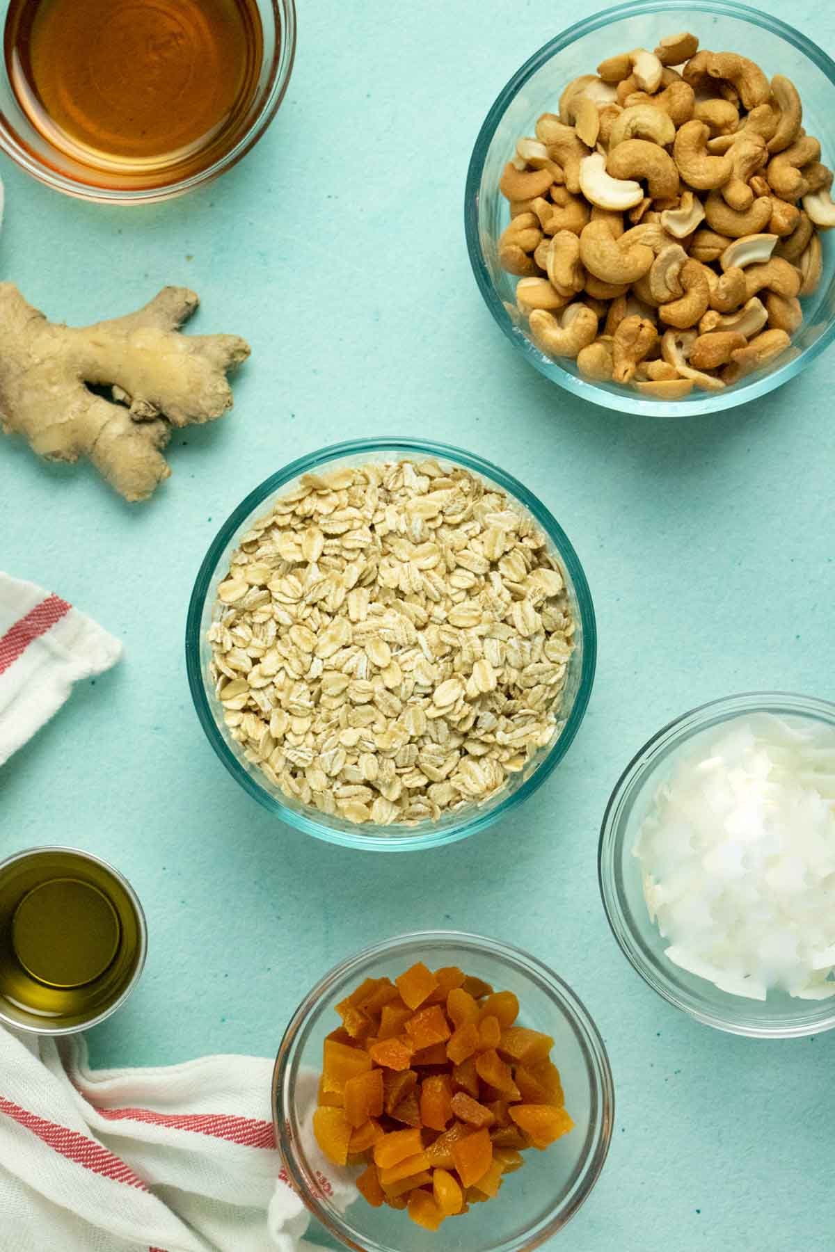 overhead photo of a blue table with bowls of rolled oats, cashews, coconut, and maple syrup with a small cup of oil and a piece of gingerroot
