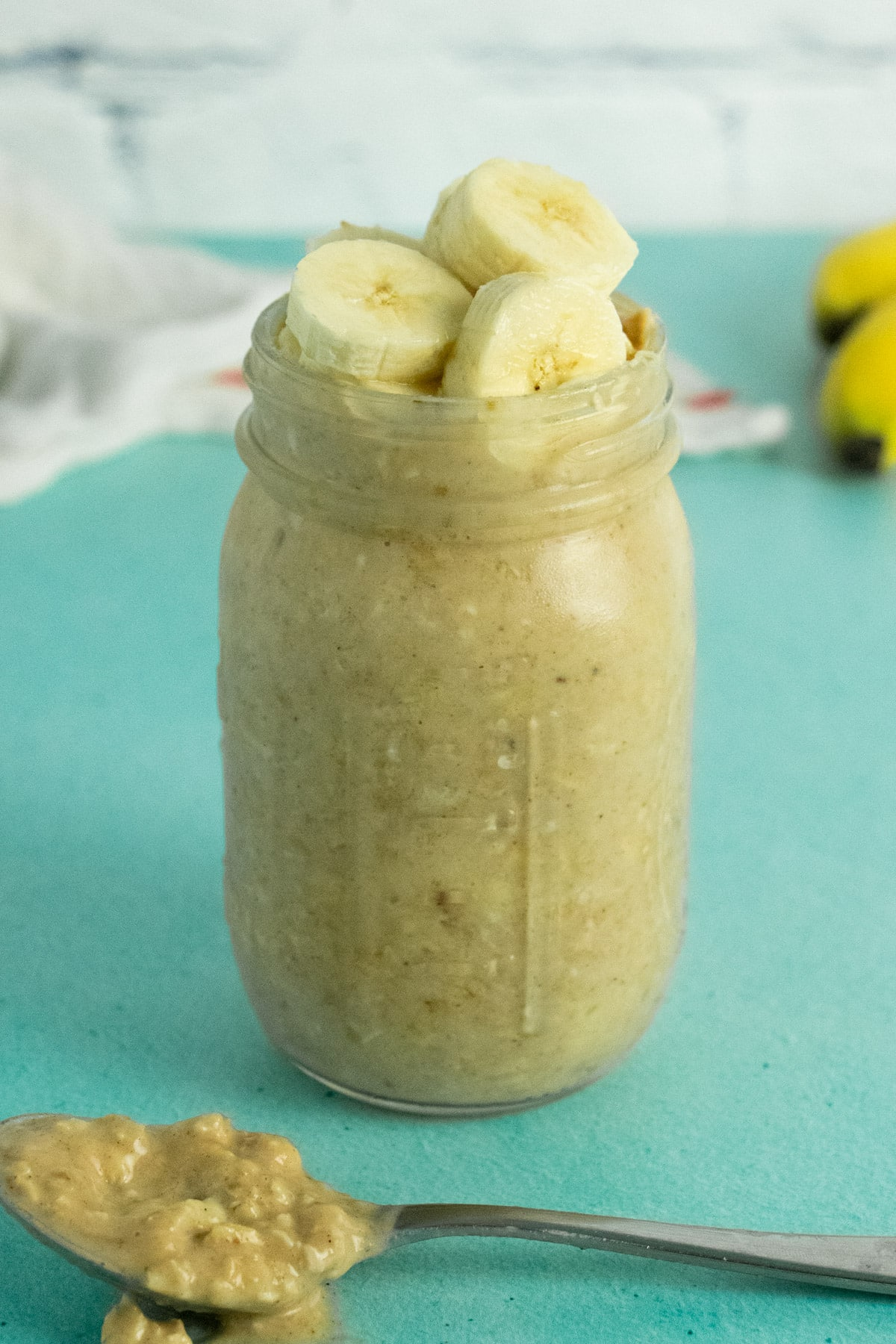 mason jar of peanut butter banana overnight oats with bananas and a tea towel in the background