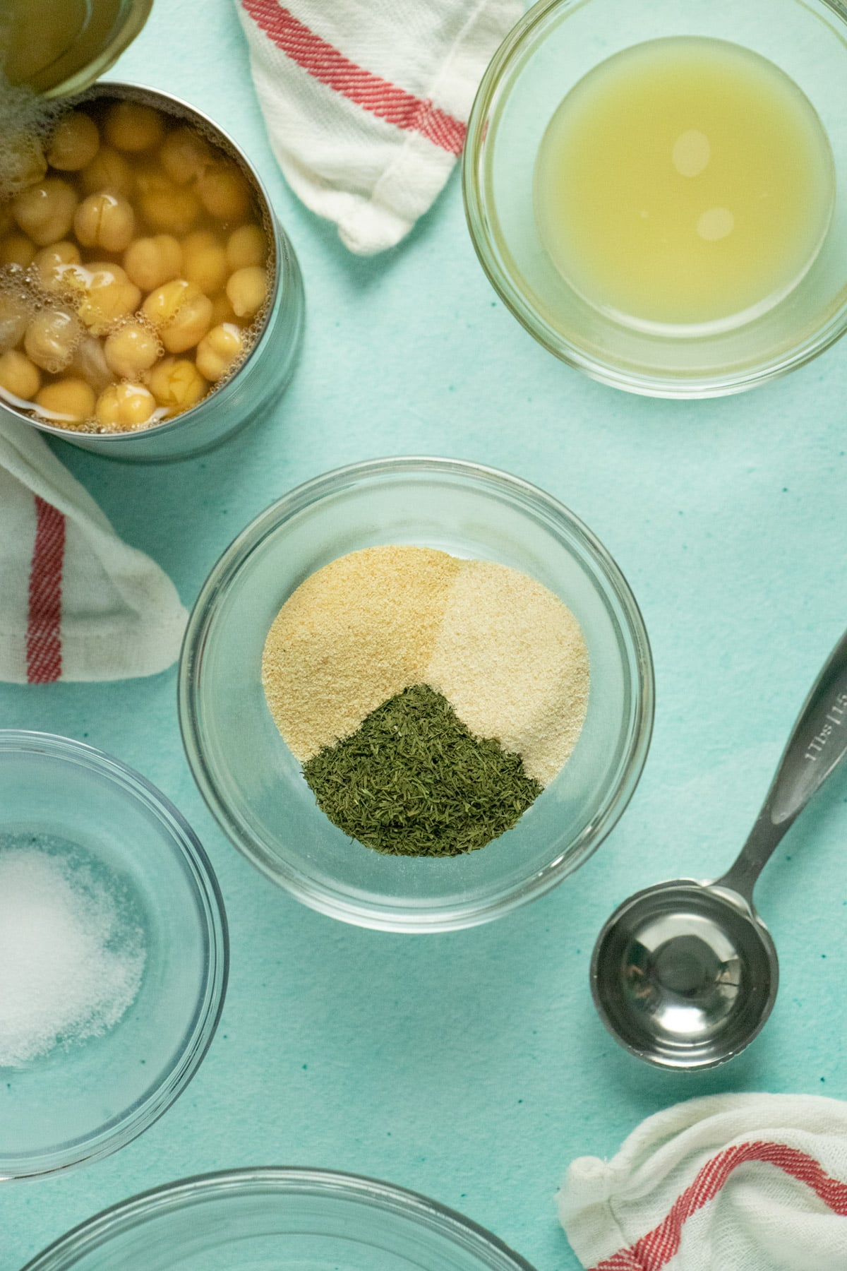 aqua table with an open can of chickpeas and bowls of spices, salt, and lemon juice and a one tablespoon measuring spoon