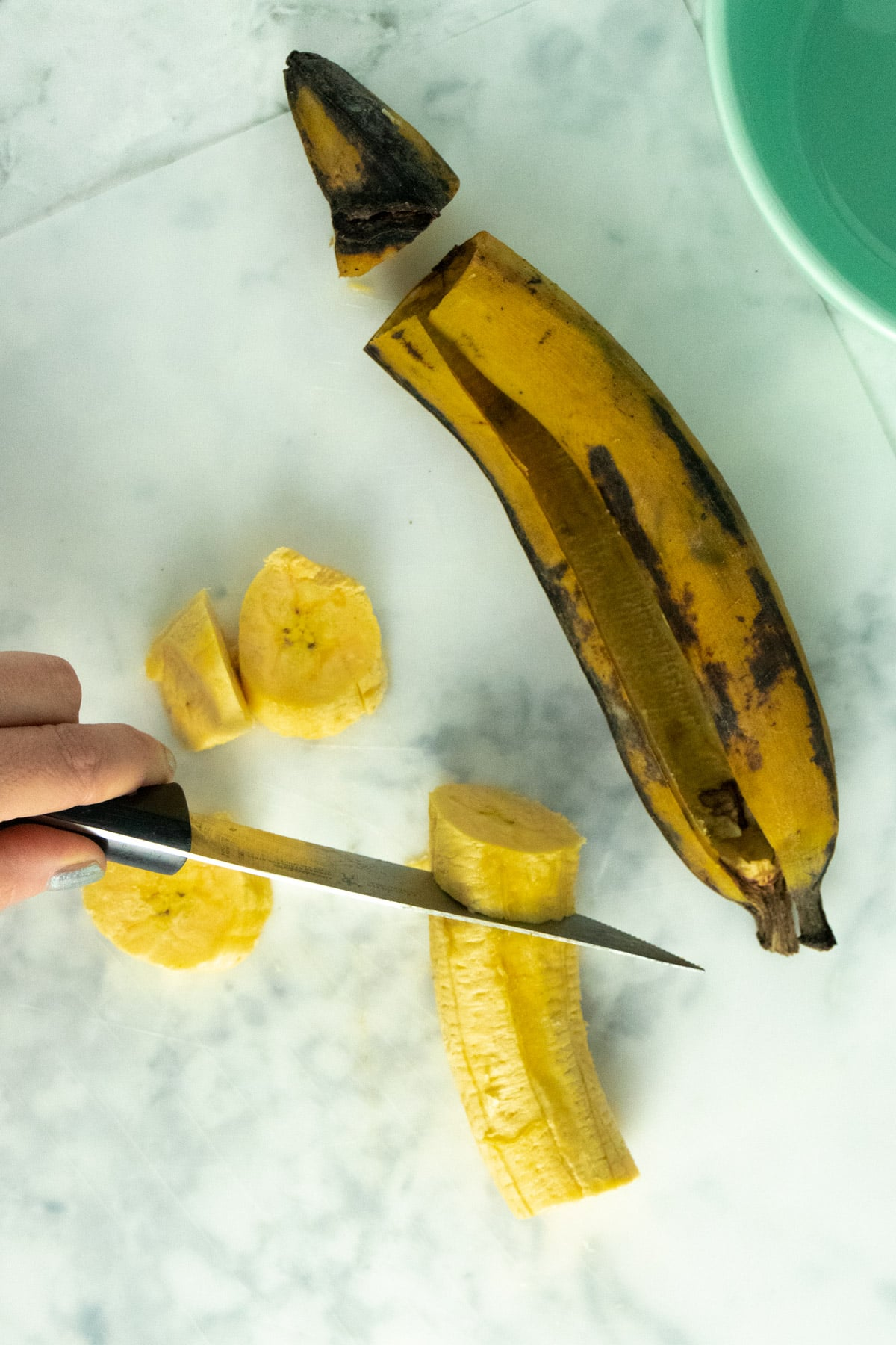 slicing plantains on an angle on a marble cutting board
