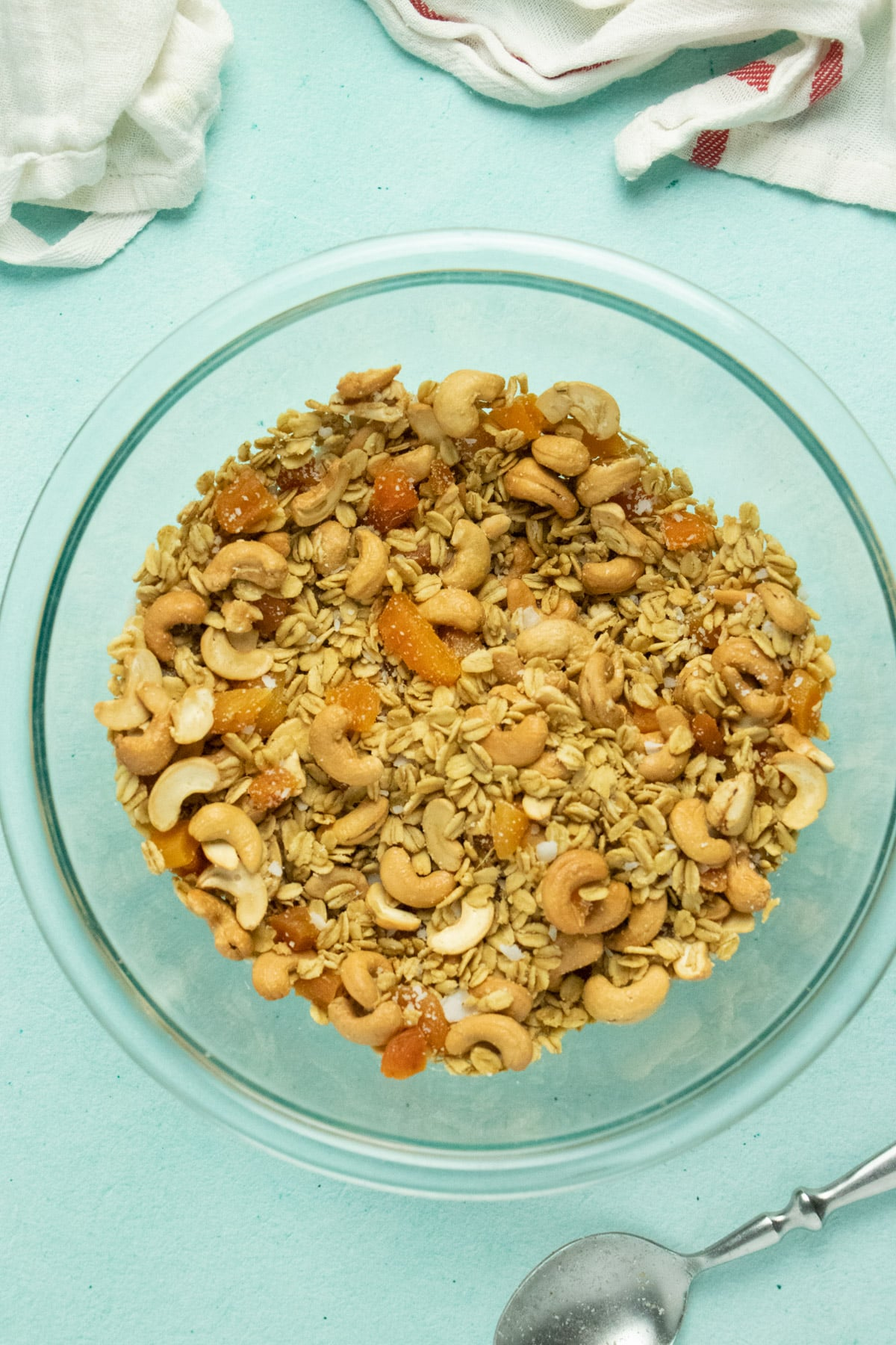glass mixing bowl of homemade ginger granola with apricots, cashews, and coconut