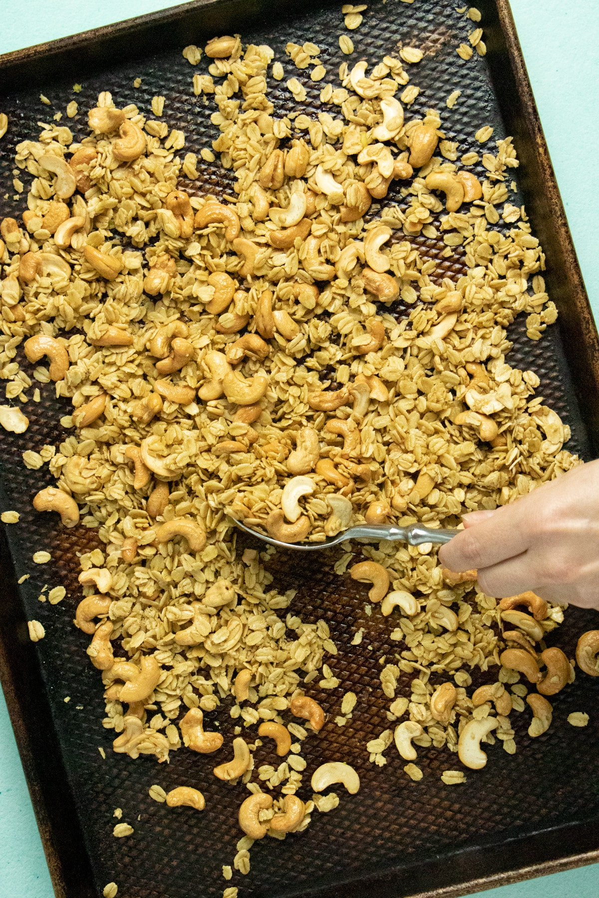 hand using a spoon to stir granola on a baking sheet during the baking process