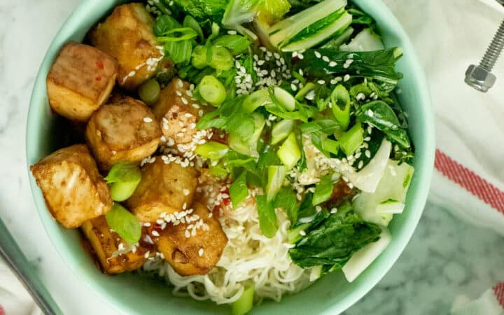 overhead photo of a crispy tofu bowl with bok choy, sweet chili sauce, noodles, sesame seeds, and green onion next to an EZ Tofu Press