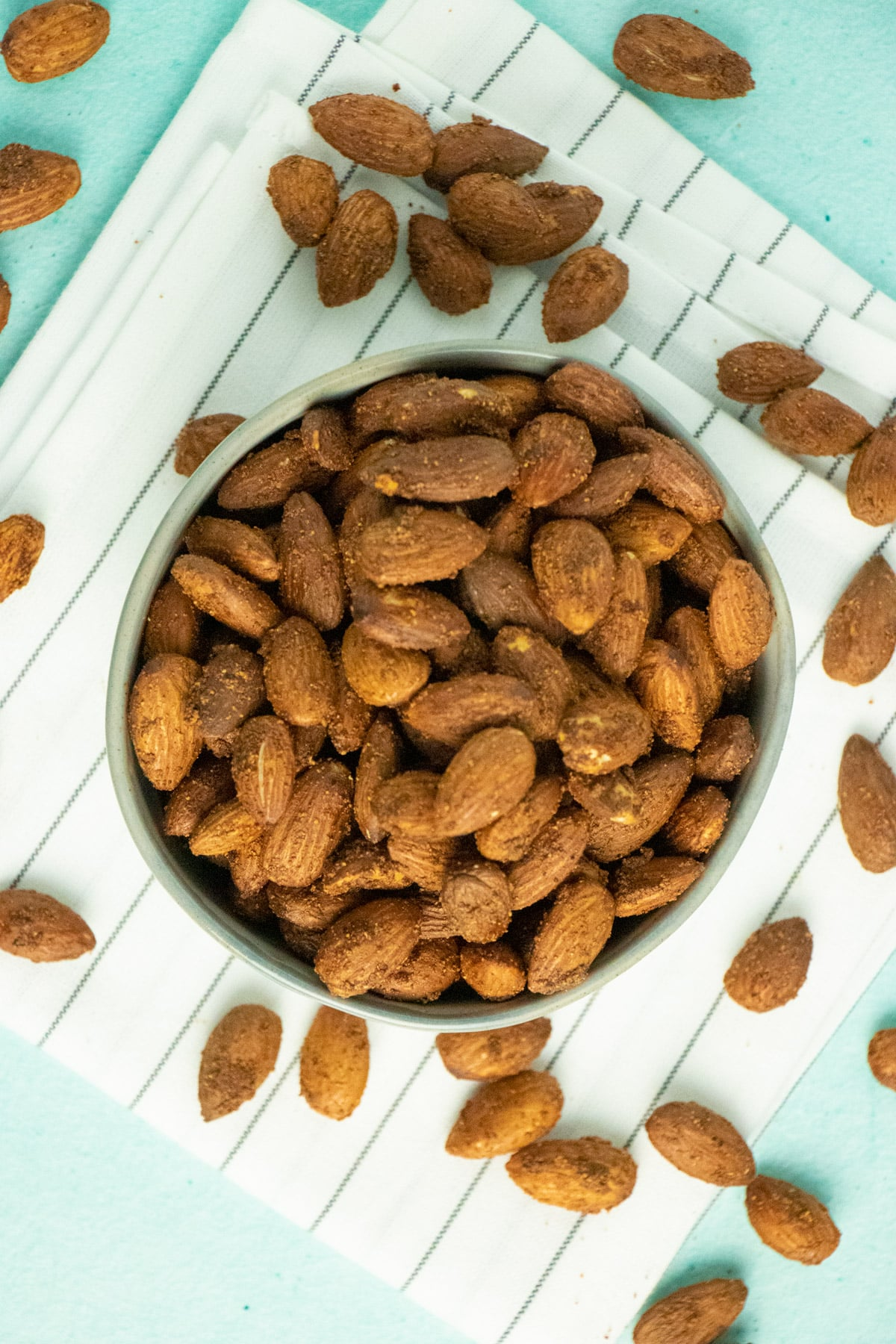 small serving bowl of garlic air fryer roasted almonds on a striped tea towel