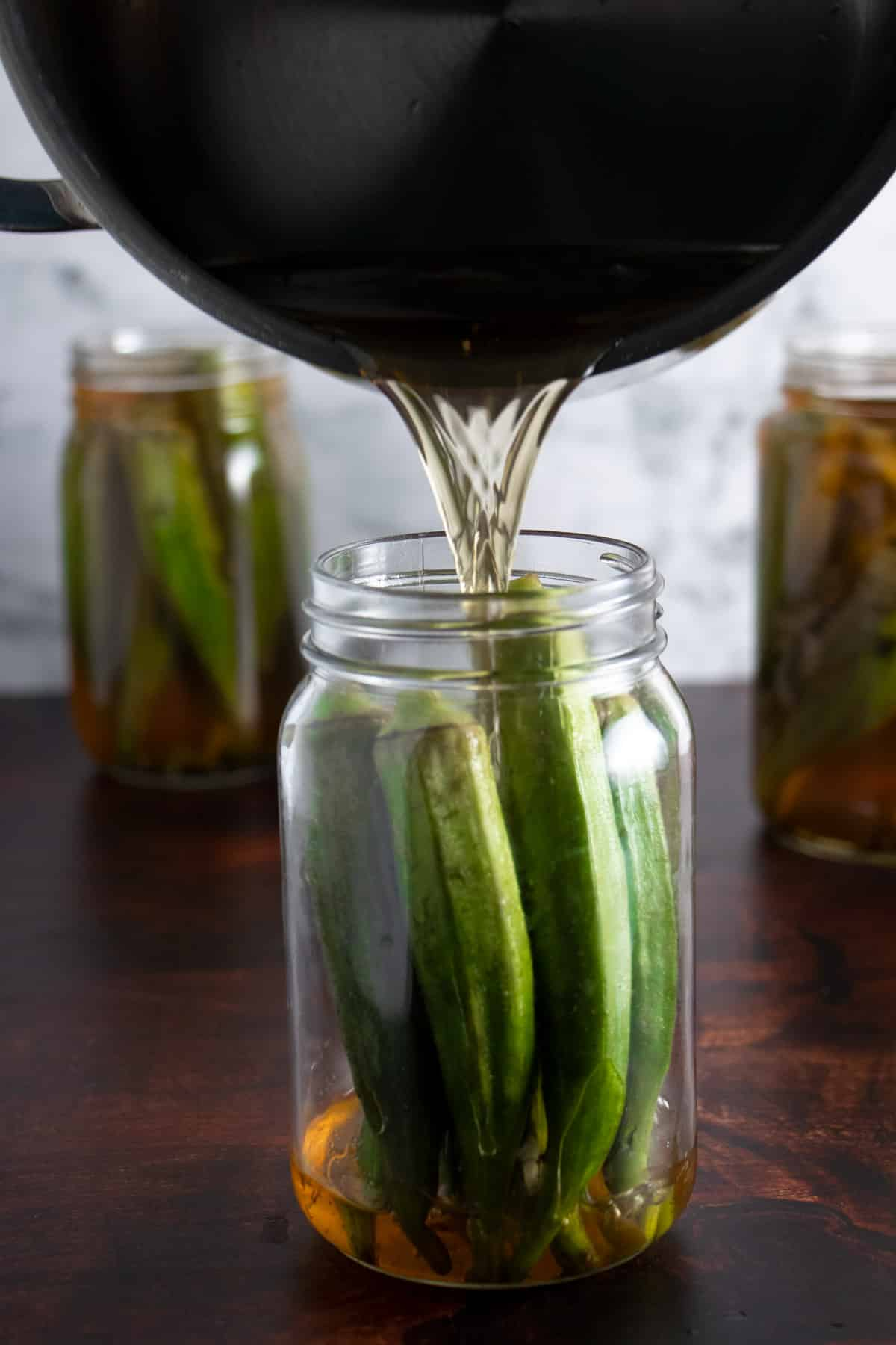pouring brine into the jars of okra