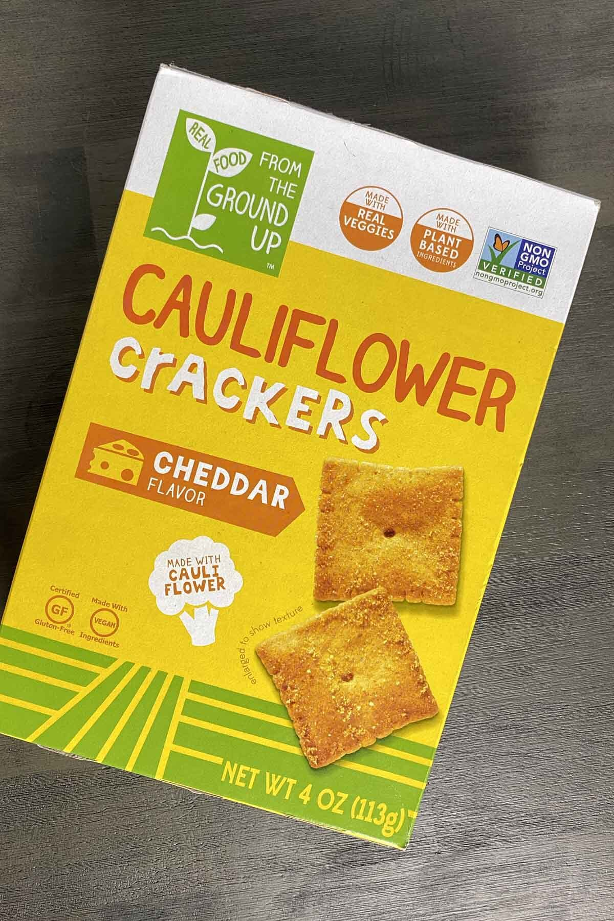 box of Real Food From the Ground UP Cauliflower Crackers, Cheddar Flavor on a gray table. Box is yellow with square, orange crackers depicted on the front