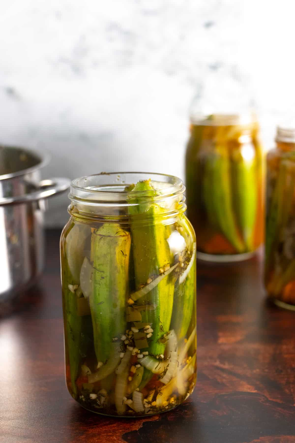 jars of pickled okra on a wooden counter with a marble backsplash
