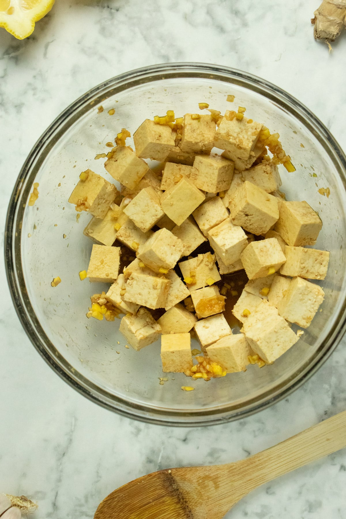 photo of cubed tofu marinating in garlic ginger, soy sauce, and lemon juice in a large bowl