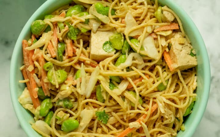 overhead photo of a bowl od noodles with carrots, cabbage, edamame, and tofu