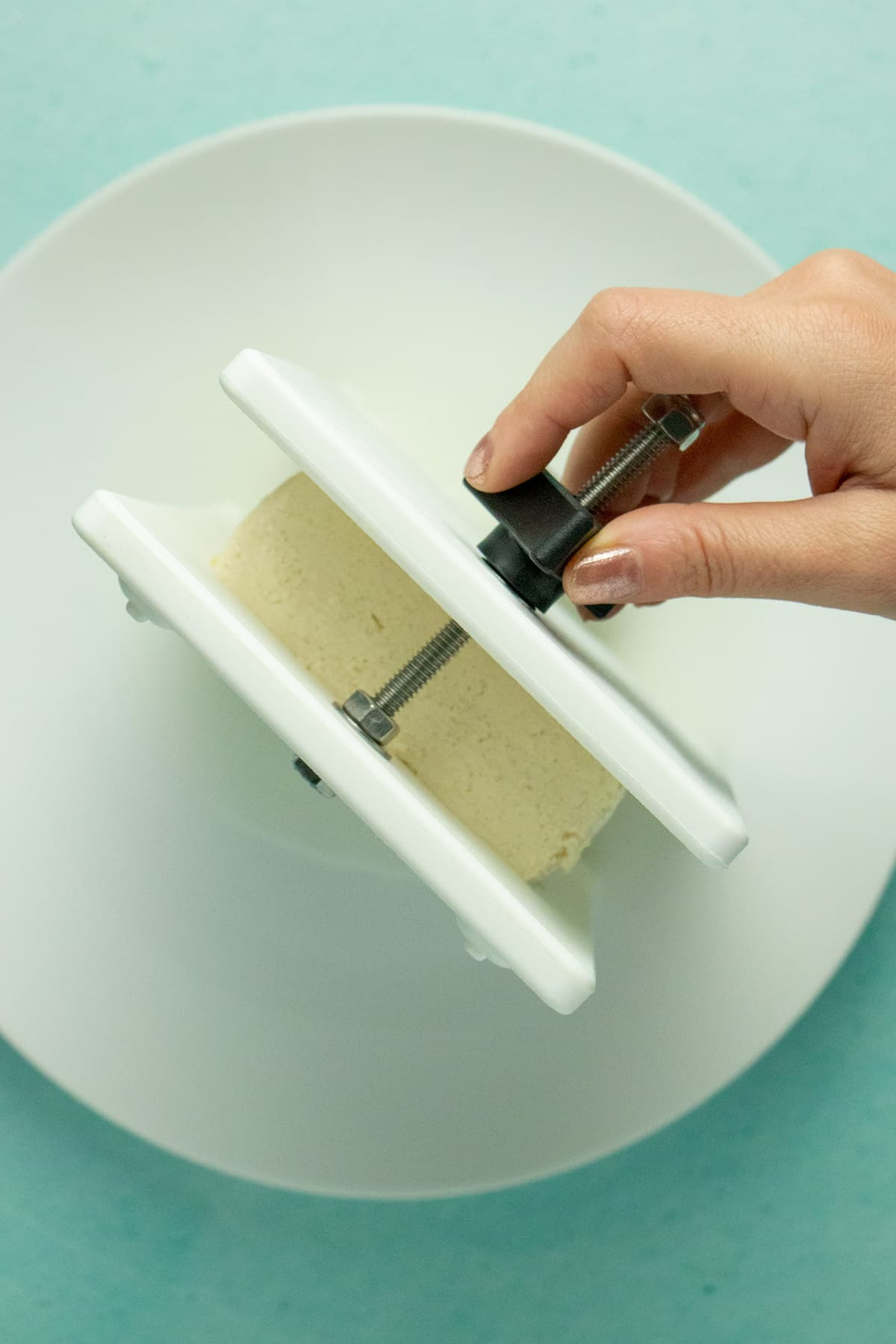 hand tightening an EZ Tofu Press with a block of tofu in it
