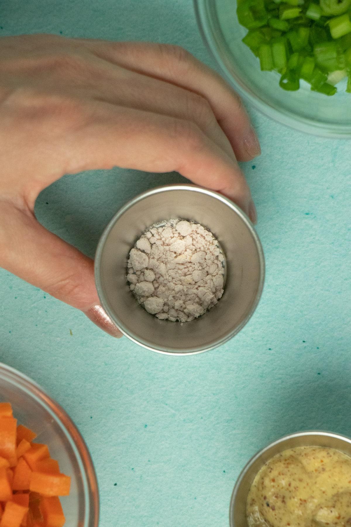 hand picking up a ramekin of black salt from a table