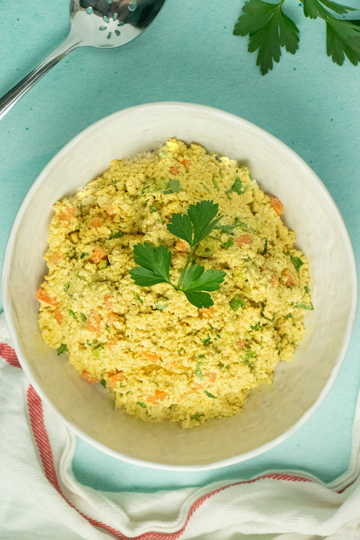 tofu egg salad in a white serving bowl with parsley garnish
