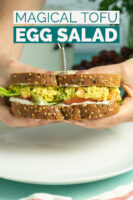 hands holding a tofu egg salad sandwich with lettuce and tomato, text overlay