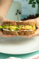 hands holding a tofu egg salad sandwich with lettuce and tomato