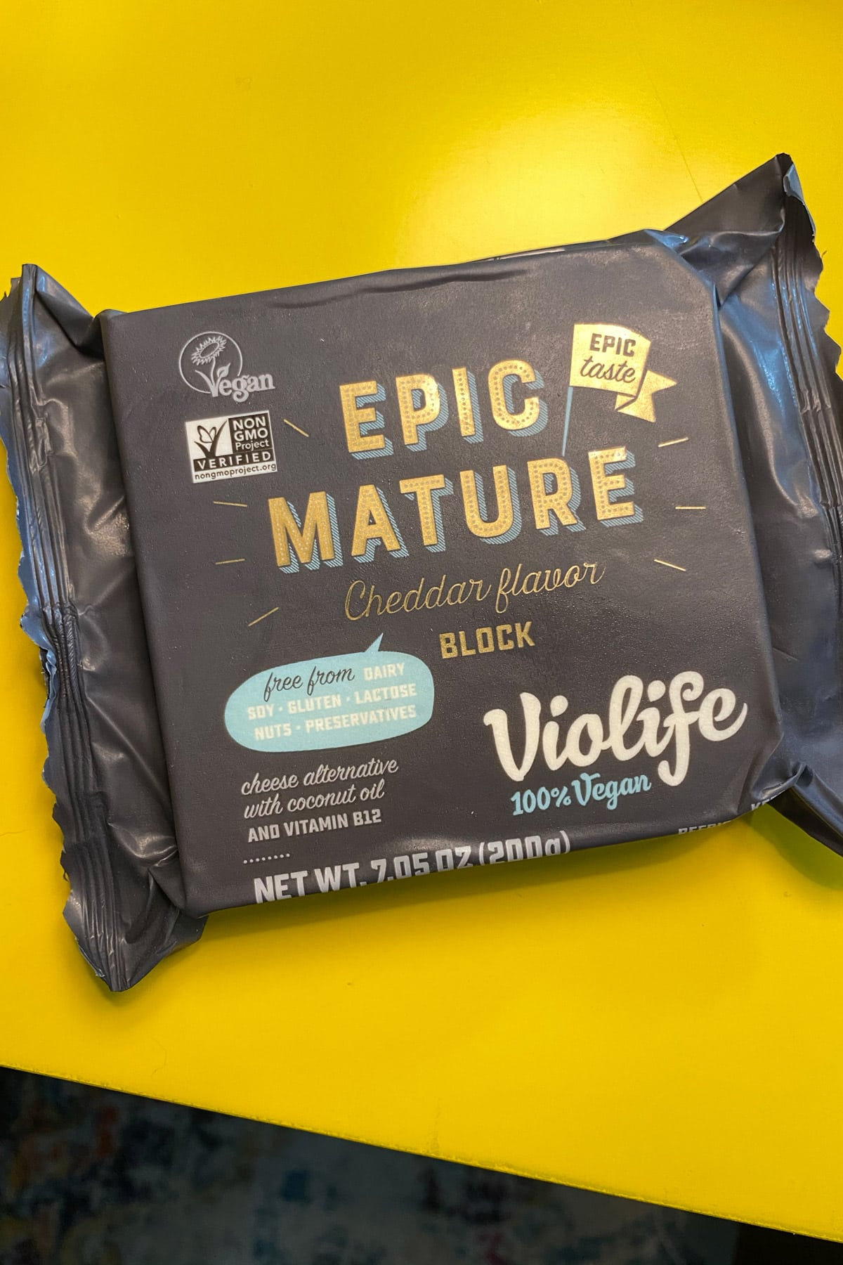 black package of a block of Violife Epic Mature Cheddar on a yellow table