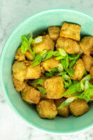 overhead photo of air fryer tofu in a blue bowl with green onions sprinkled on top
