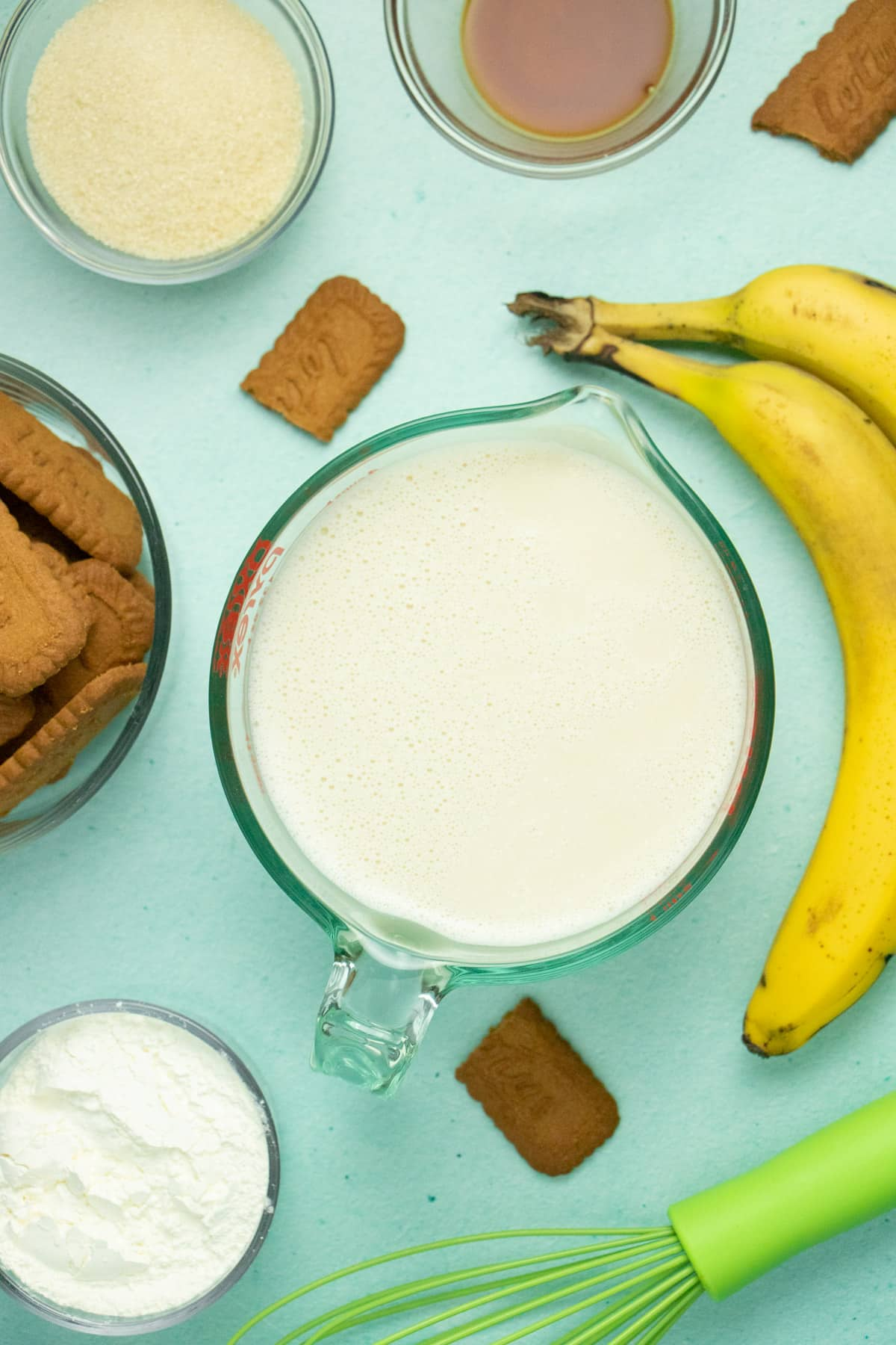blue table with measuring bowls of oat milk, cornstarch, sugar, and vanilla next to bananas and Biscoff cookies