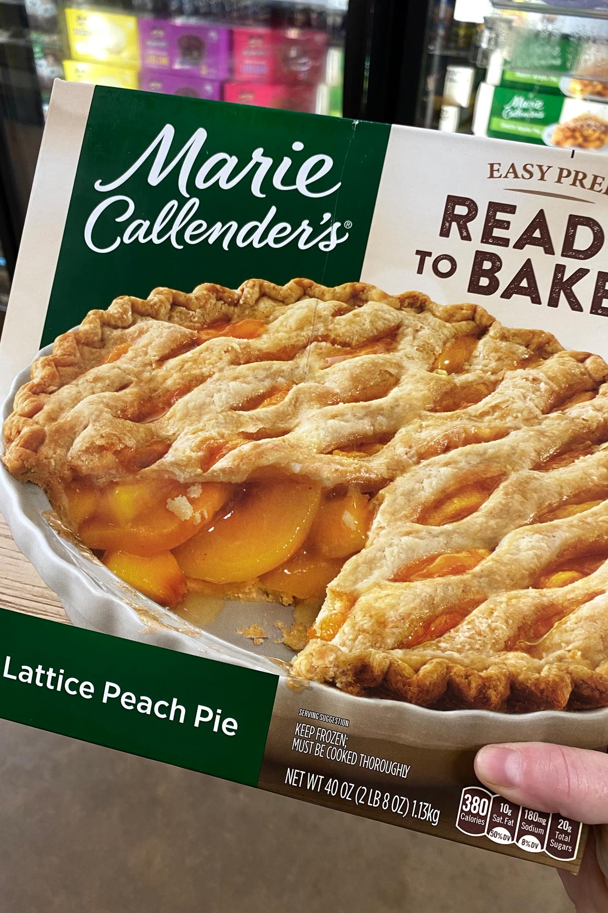hand holding a package of Marie Callender's Lattice Peach Pie in the freezer aisle of a grocery store