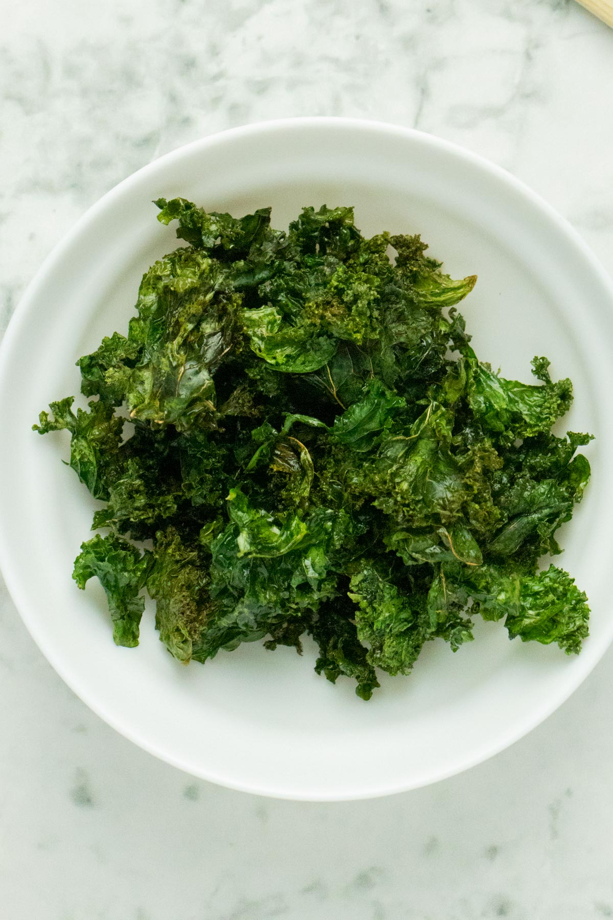 kale chips in a bowl before seasoning