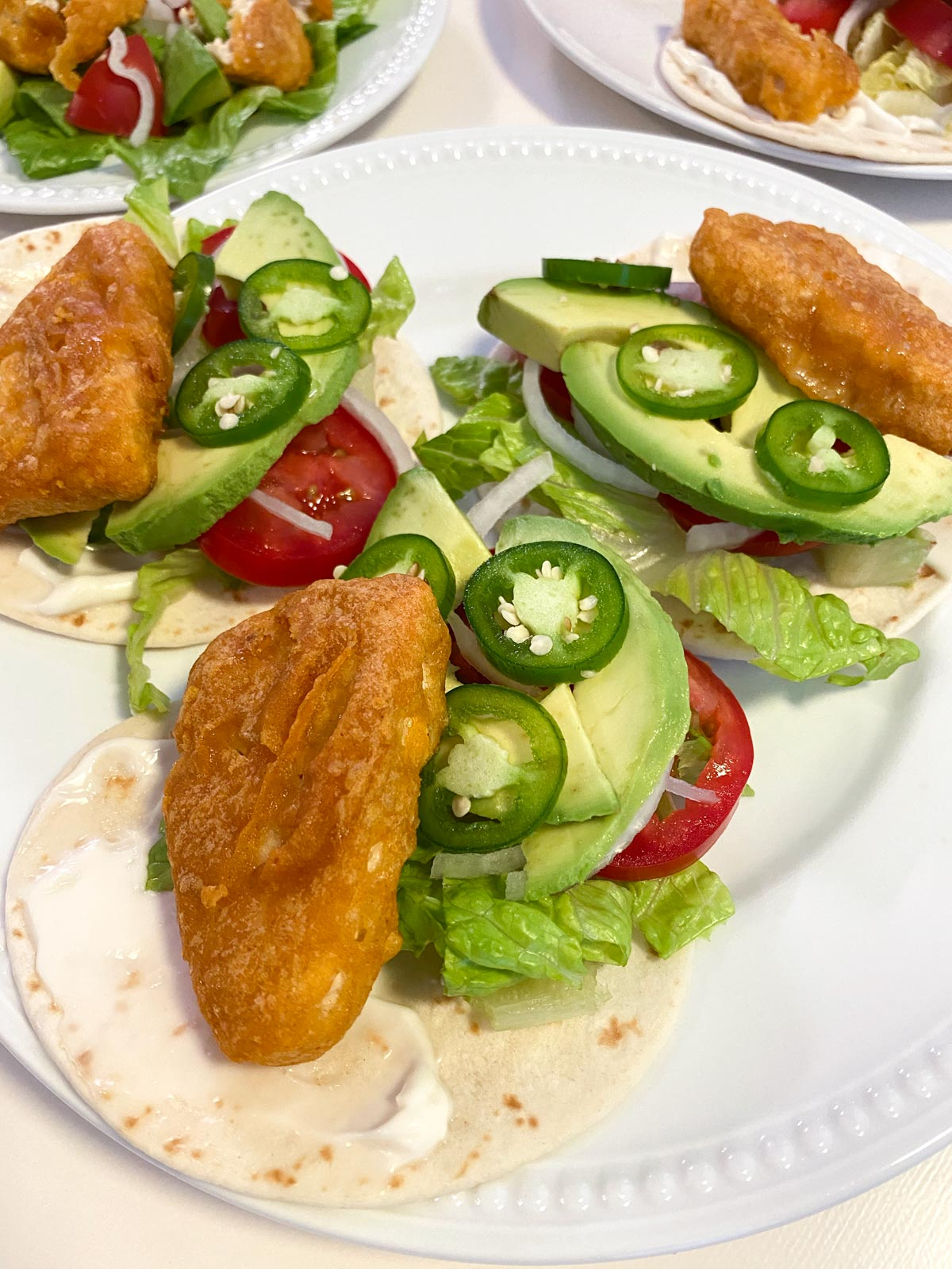 fishless tacos with lettuce, tomato, onion, jalapeno, and avocado