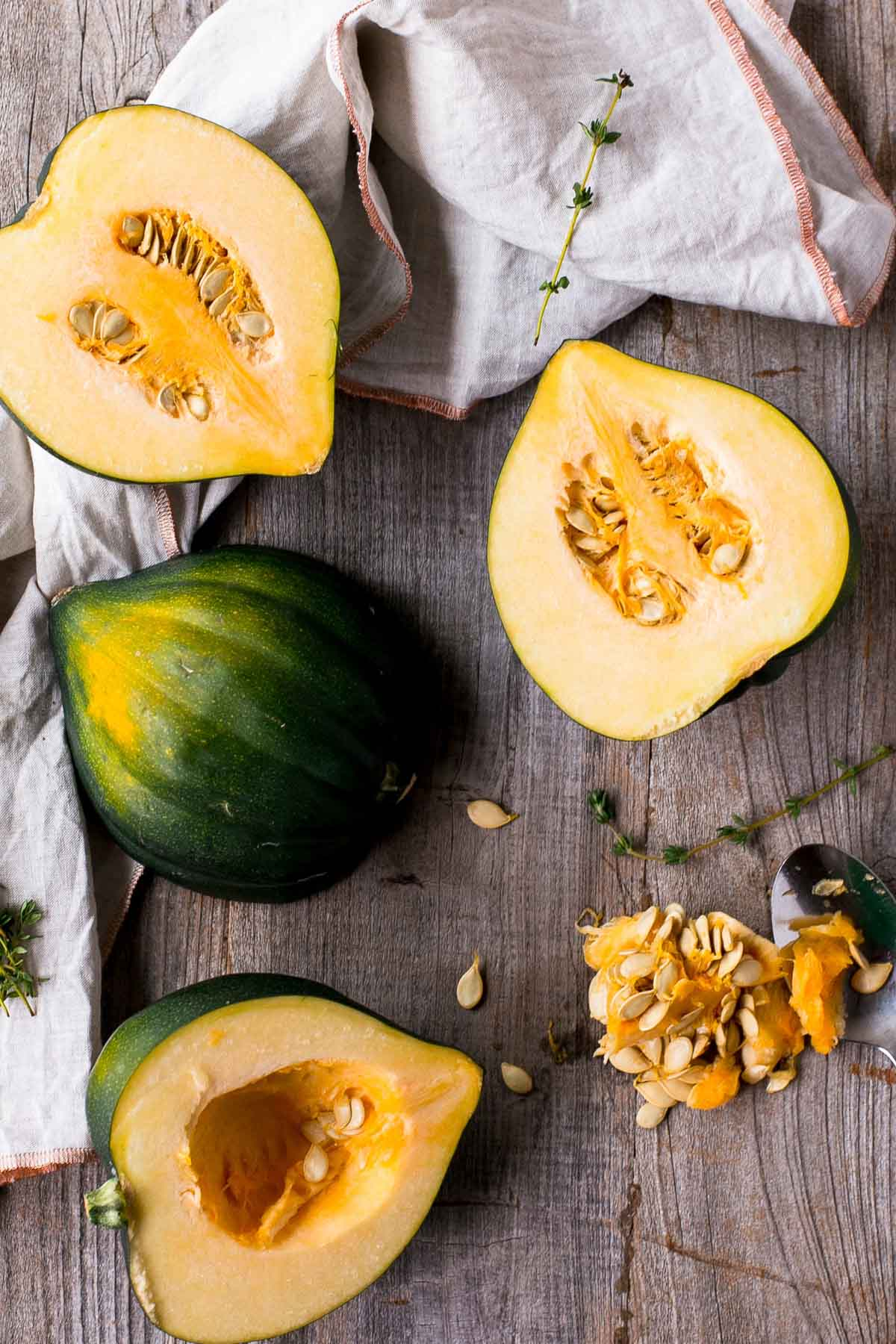 cut acorn squash on a wooden cutting board with thyme leaves