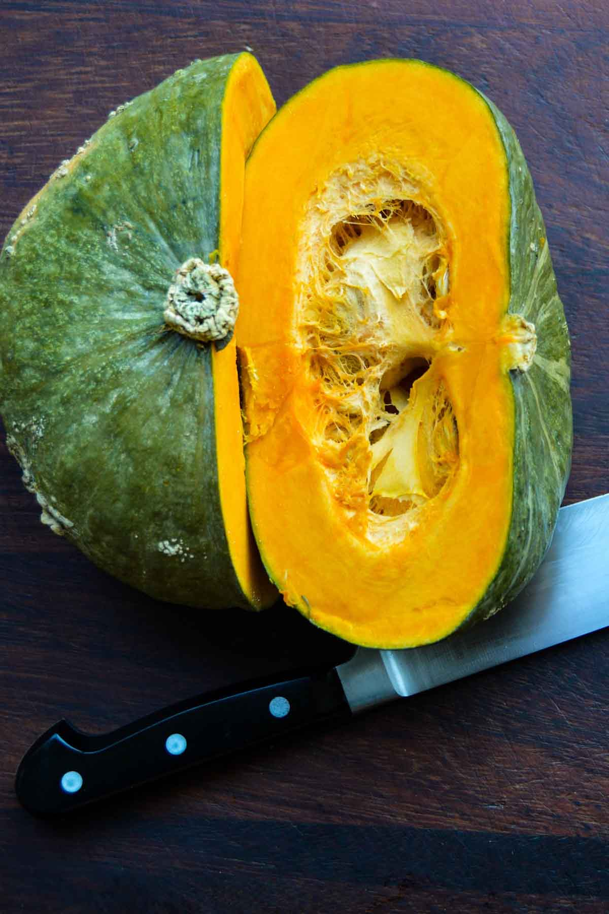 halved buttercup squash on a dark wooden cutting board