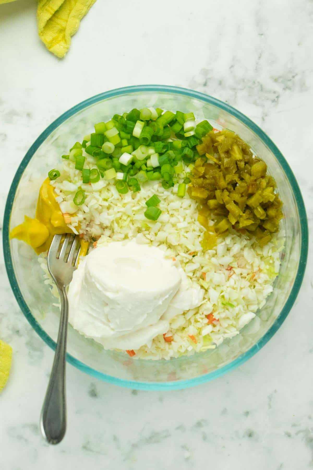 cabbage in a mixing bowl with vegan mayo, yellow mustard, green onion, and pickled jalapeno