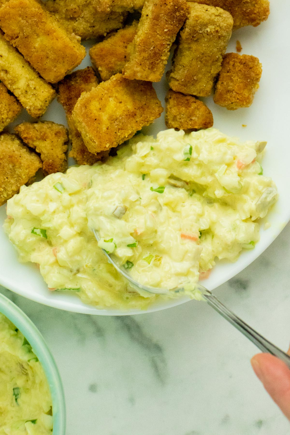 spooning vegan jalapeno slaw onto a plate with chicken fried tofu