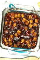 glass baking pan of sticky BBQ tofu on a marble table