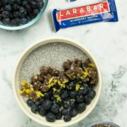 blueberry lemon chia breakfast bowl on a marble table next to Larabars and blueberries