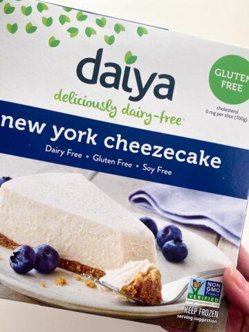 hand holding a box of Daiya New York Cheezecake