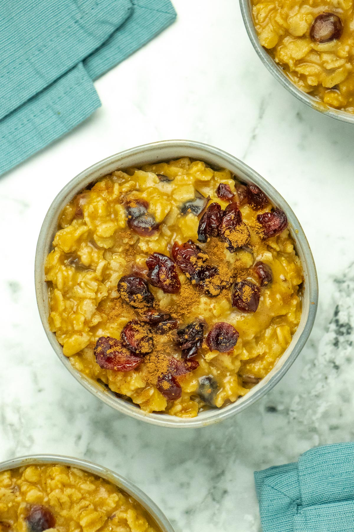 bowls of pumpkin oatmeal with cranberries and pumpkin spice