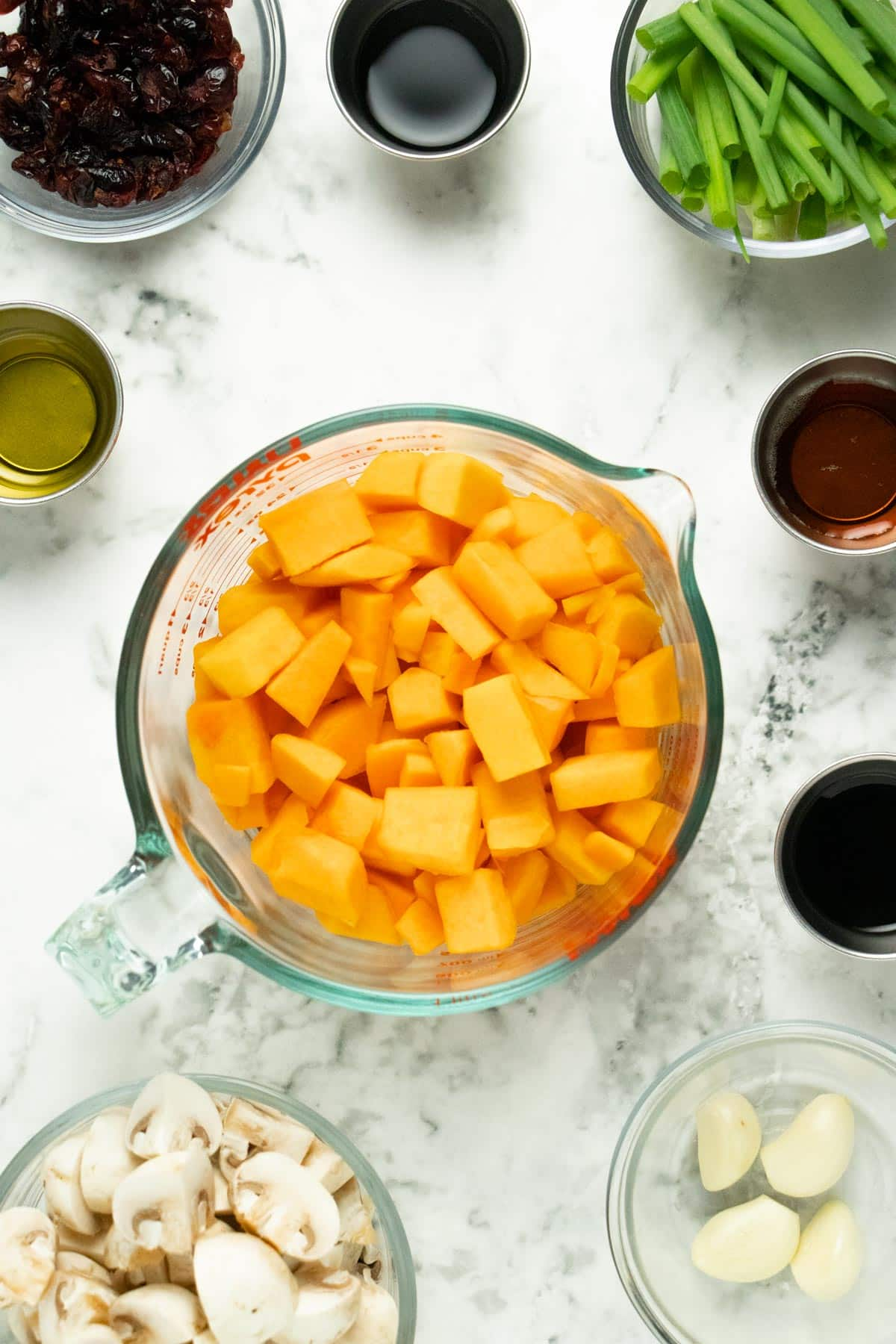 diced butternut squash in a glass mixing bowl surrounded by bowls of other ingredients