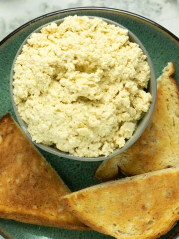 bowl of tofu ricotta on a plate with toast points
