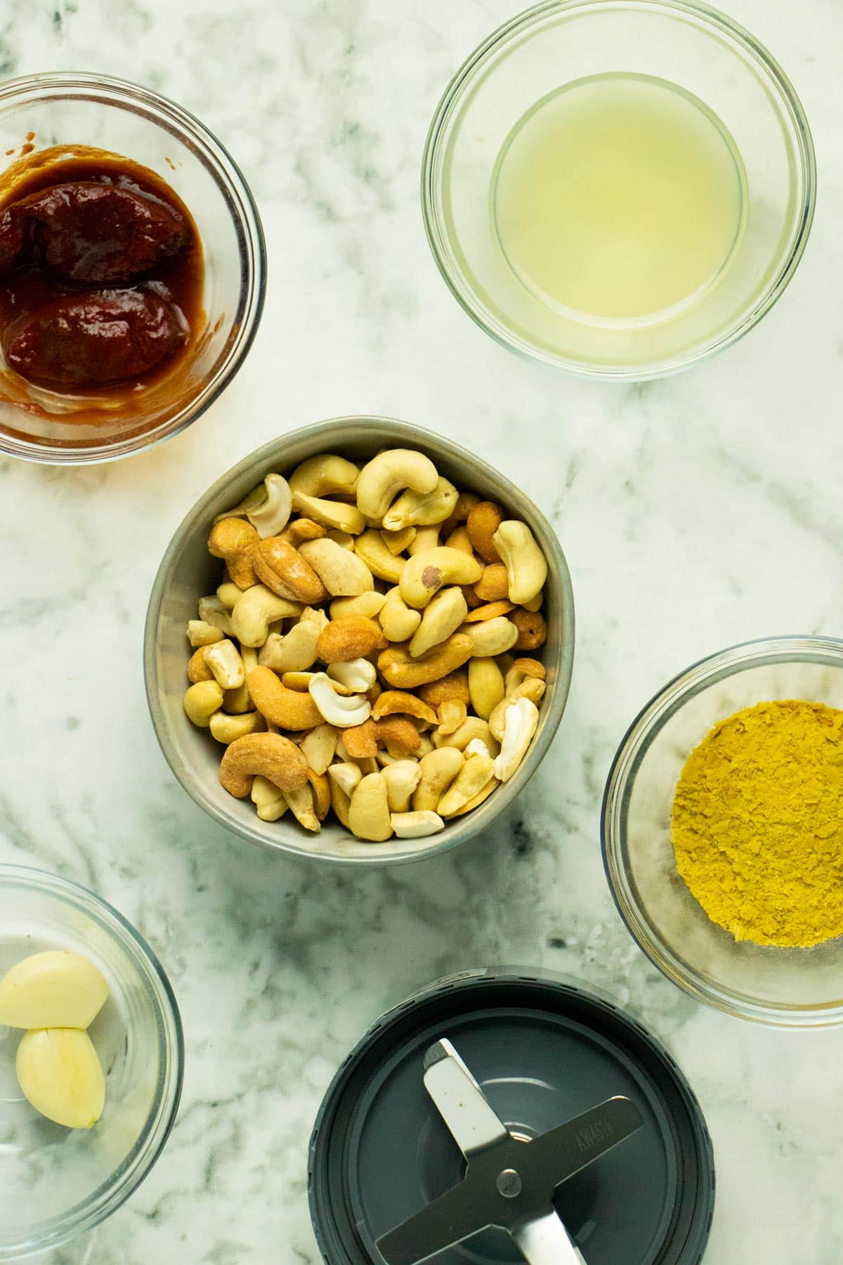 bowl of cashews surrounded by bowls of the other sauce ingredients