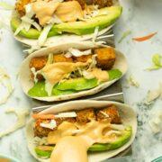 spooning chipotle sauce onto crispy tofu tacos