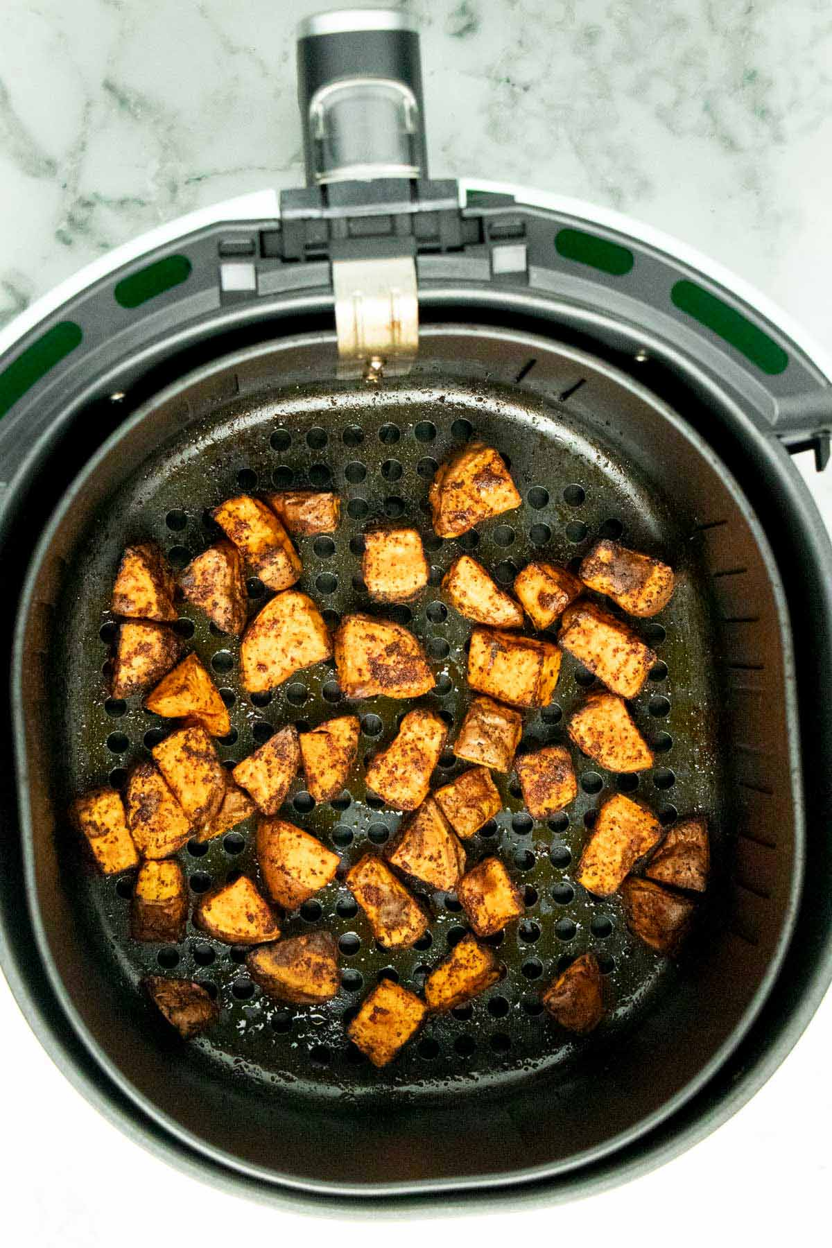 cooked sweet potato chunks in the air fryer basket