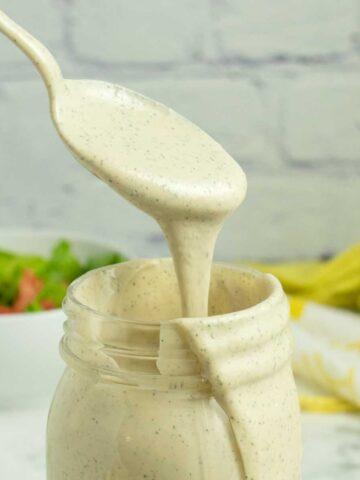 spooning tahini ranch dressing out of a mason jar