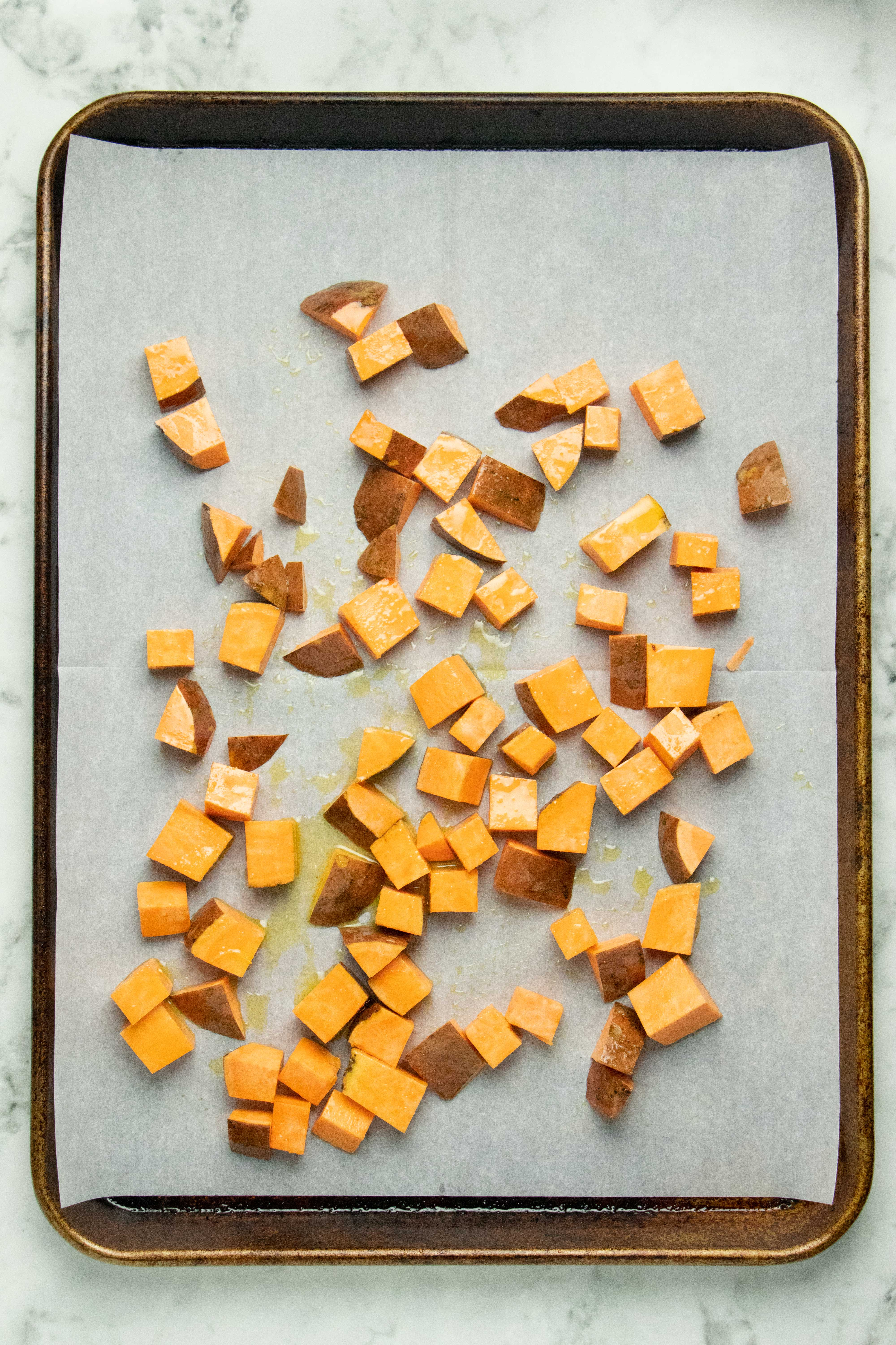 sweet potato chunks on a baking sheet, ready for the oven