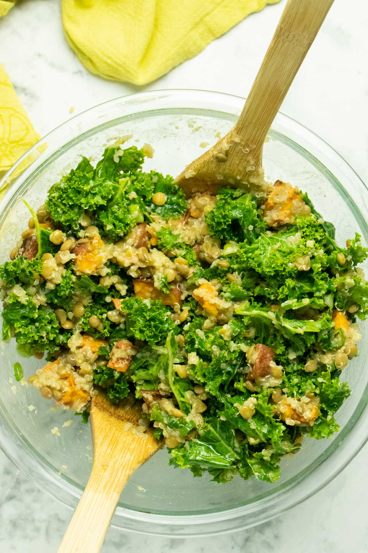 lentil quinoa kale salad tossed together in the mixing bowl