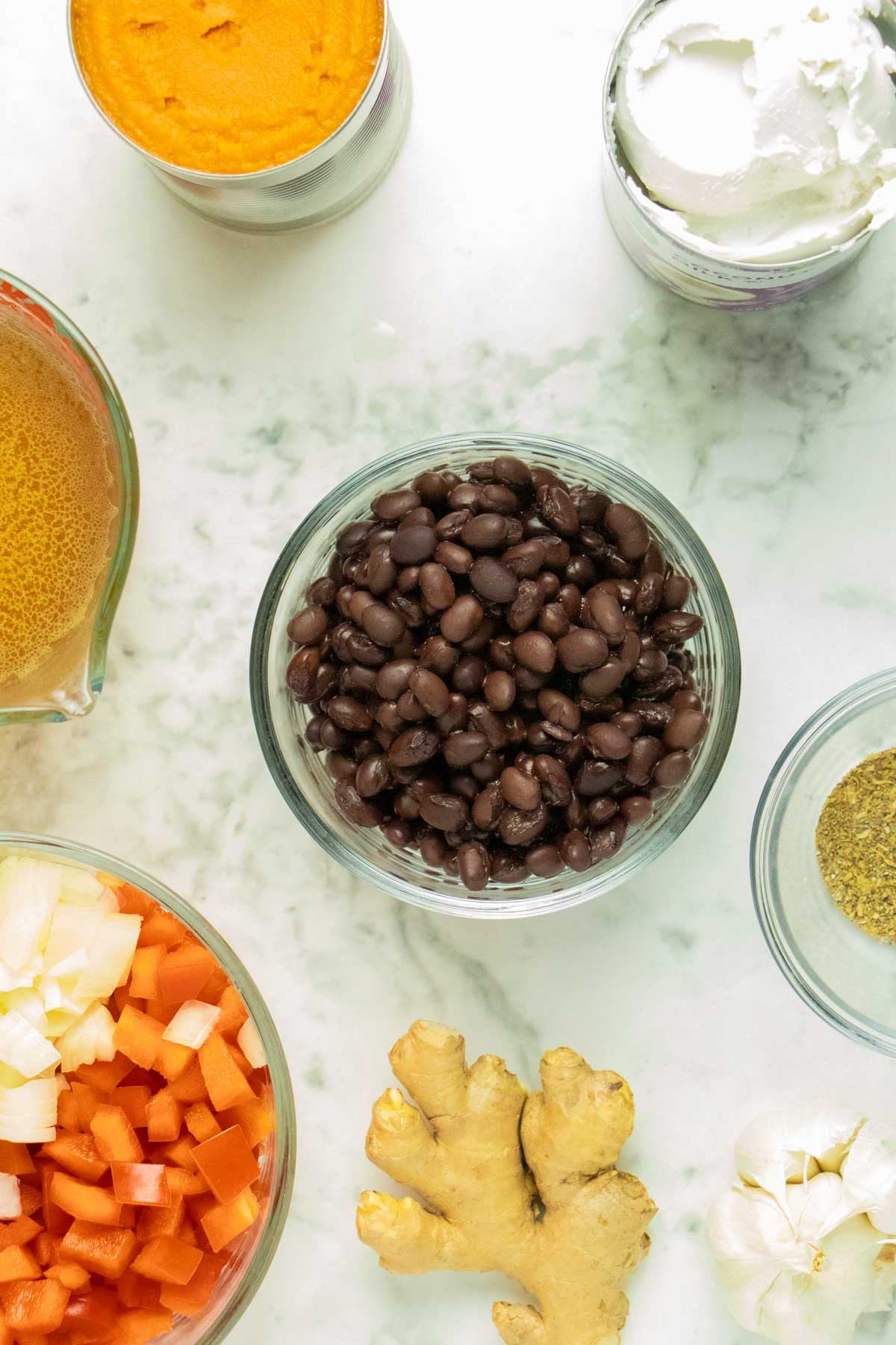 bowl of black beans surrounded by the other soup ingredients on a marble table
