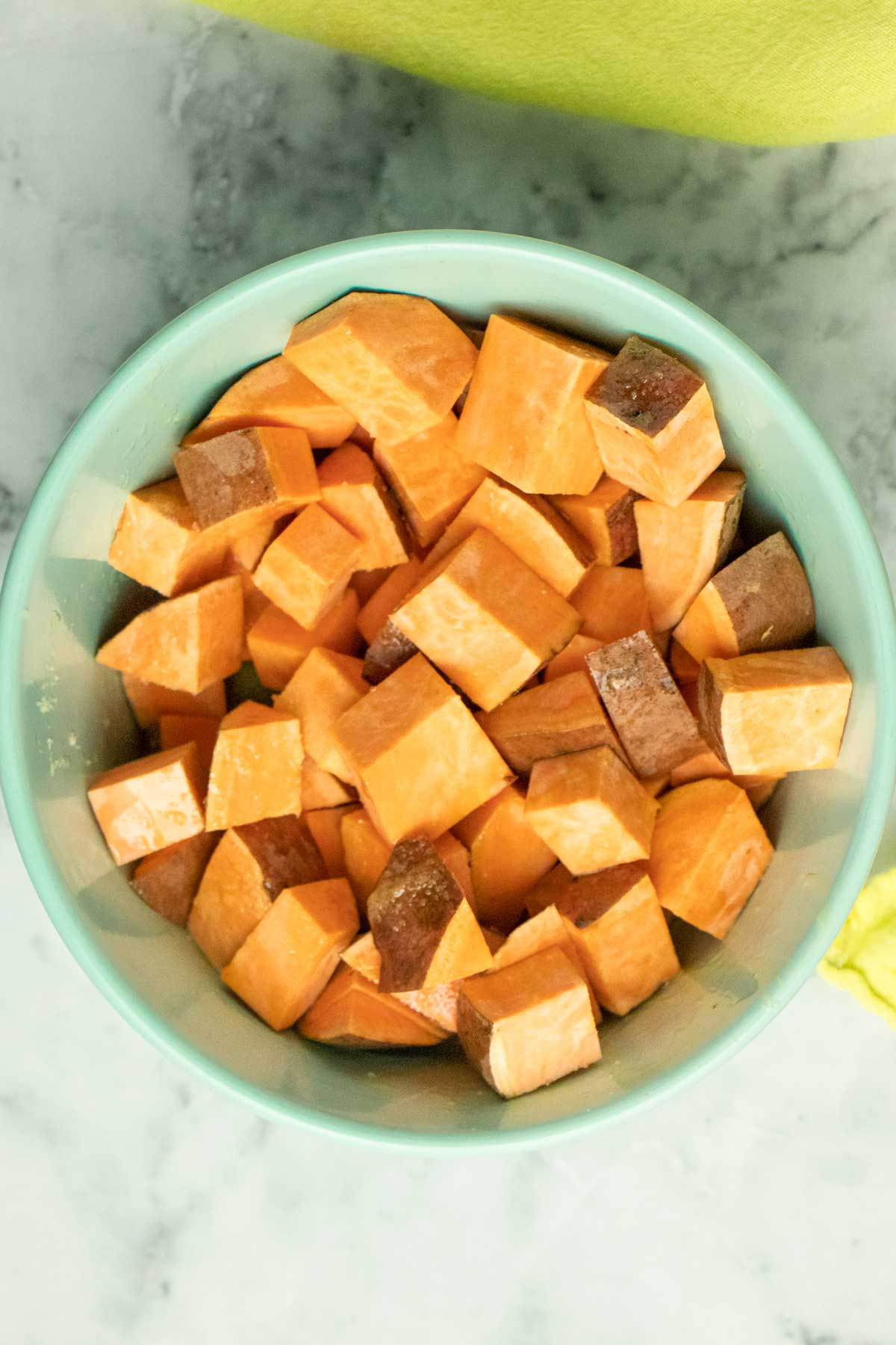 chunks of sweet potato tossed with oil and salt in a bowl